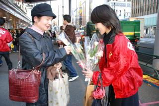 RENGO member hands out roses (near Marion in Yurakucho district of Tokyo)